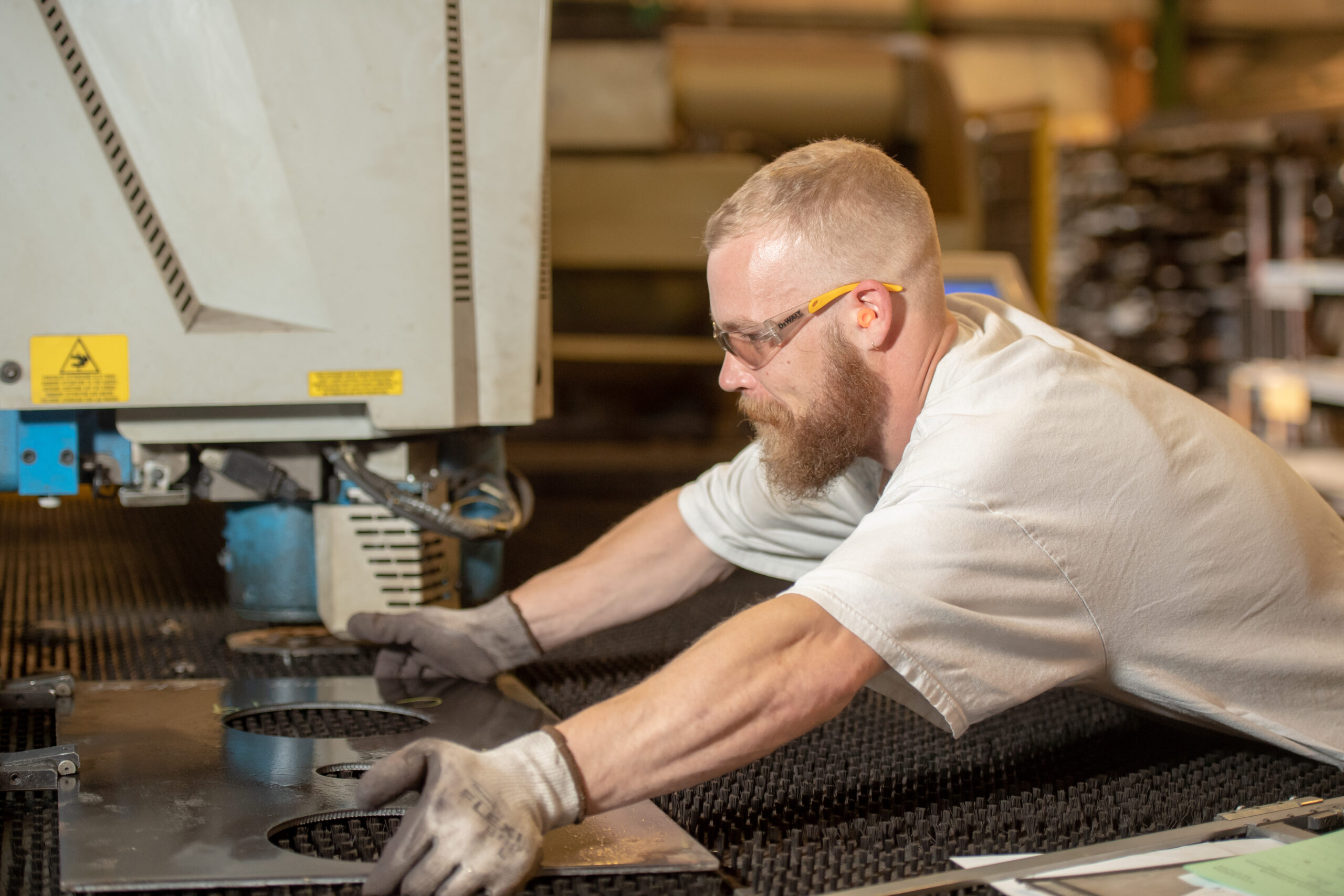 worker running a punch press machine